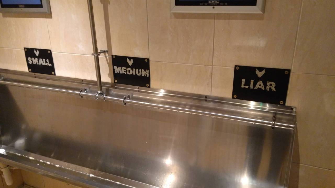 Signs above the public urinal